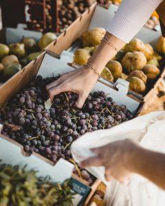 Des mains qui empoignent des raisins au marché