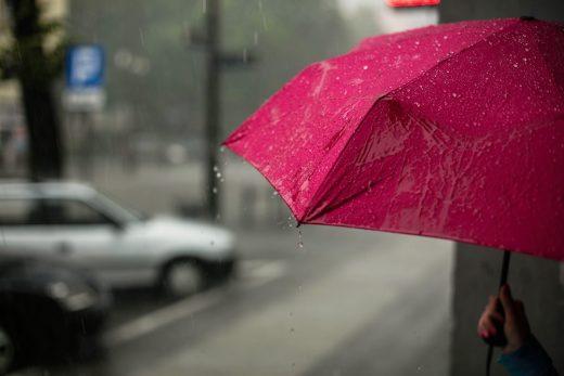 Un parapluie rose sous la pluie, dans une ville au petit matin
