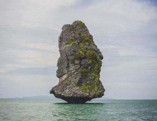 Un rocher au milieu de l'eau qui menace de s'effondrer