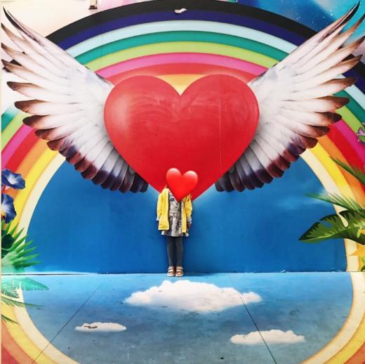 Fillette devant un tag de coeur qui s'envole street art à Toulouse
